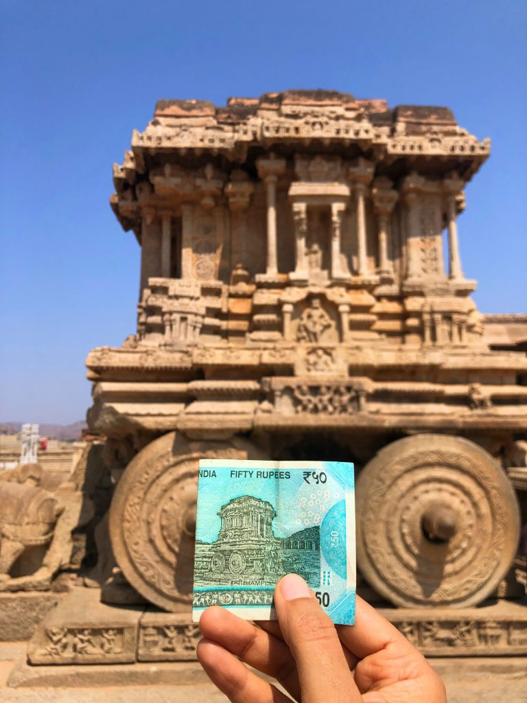 A picture of a 50 rupee note against an ancient site