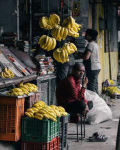 A man sits outside a smalls shop (micro-enterprise) that sells knick-knacks